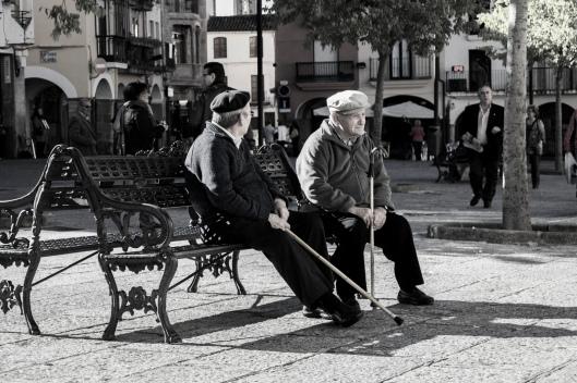 Dos ancianos viendo pasar a la gente del pueblo
